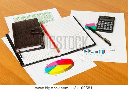 Calculator, notepad, pen and pencil on the background of the desktop.