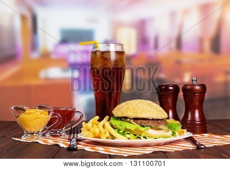 Hamburger, french fries, glass of cola, sauces and spices on a table in a cafe.