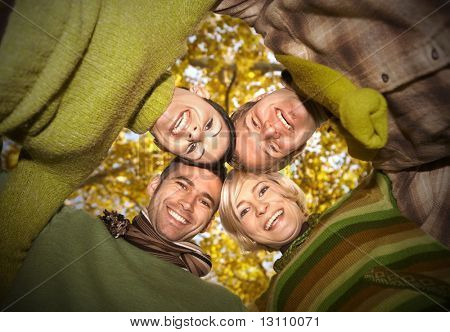 Group of happy friends standing with their heads together in autumn forest, smiling. Low angle view.?