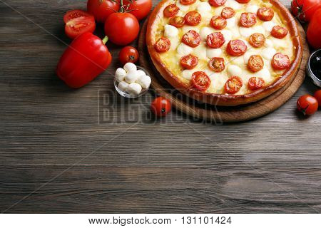 Pizza Margherita with vegetables on wooden table