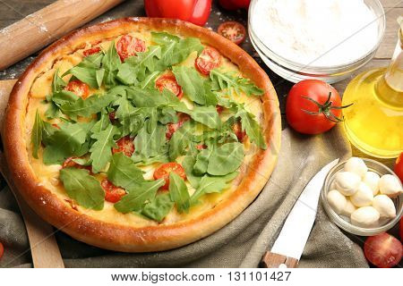 Pizza Margherita with arugula and kitchenware on wooden table