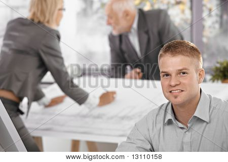 Young office worker in focus smiling at camera, architect colleagues working in background.?
