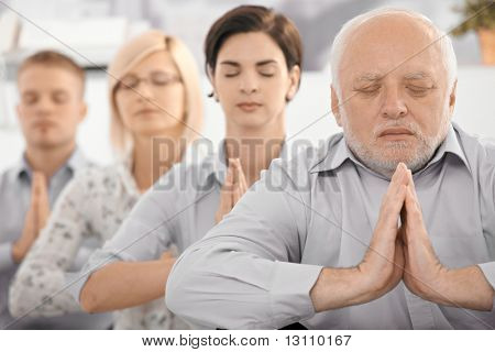 Portrait of meditating businessteam, with senior businessman in focus, exercising with closed eyes.?