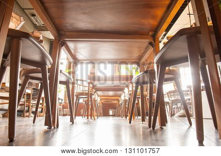 Low angle of restaurant floor under the table near wooden chairs