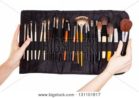 Cover with cosmetic brushes in female hands isolated on white background.