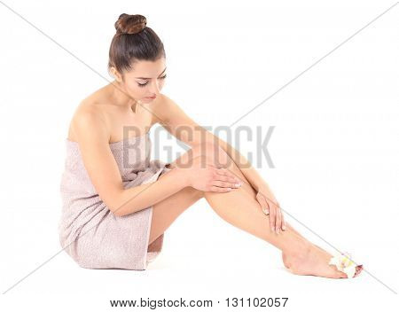 Beautiful young girl wrapped in a towel, isolated on white