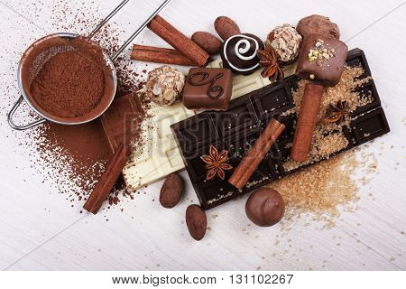 Spilled sugar and cocoa with chocolates on wooden background