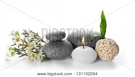 Spa still life with pebbles, flower and candle isolated on white