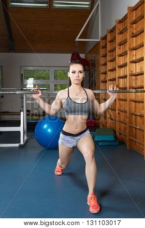 Young beautiful woman with bar in the gym
