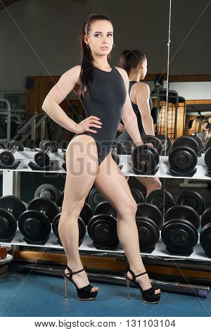 Beautiful body builder posing near dumbbells stand and mirrow in the gym