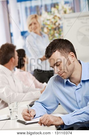 Young businessman sitting at table in office meeting room writing business notes.?