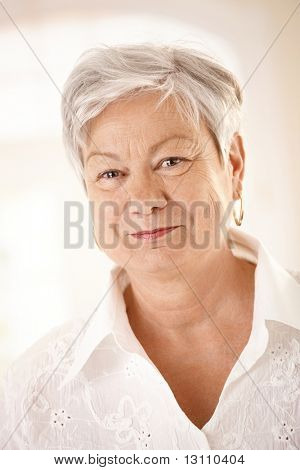 Closeup portrait of elderly woman with white hair, looking at camera, smiling.?