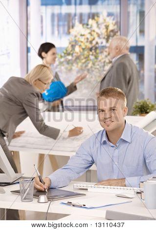 Junge Designer sitzen am Schreibtisch, Kollegen, die im Hintergrund des hellen Büros arbeiten.?