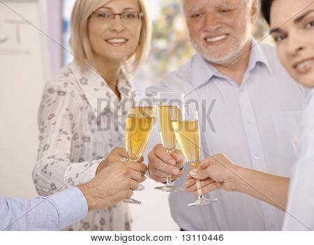 Businesspeople celebrating success with champagne, smiling, focus on glasses and hands.?