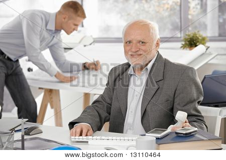 Senior businessman sitting at desk, smiling at camera, young architect working in office background.?