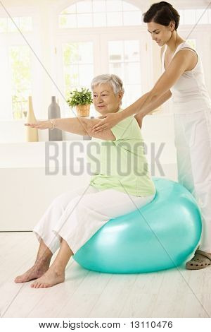 Personal trainer assisting senior woman doing fit ball exercise at home, smiling.?