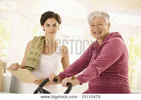 ¿Anciana sana en casa entrenamiento con bicicleta, asistido por personal trainer.?