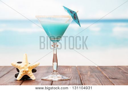 Cocktail with umbrella and starfish on a sea background.