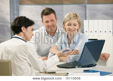 Medical doctor showing results to patients on computer in office.?