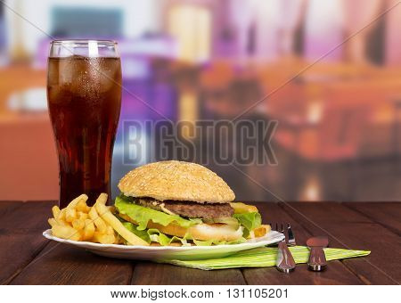 Hamburger, french fries, a glass of cola and cutlery on the background of the hall cafe.