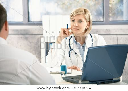 Doctor listening to patient with concentration, sitting at desk in office.?
