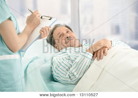 Nurse holding clipboard, taking notes of old patient lying in hospital bed.?