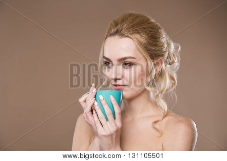 young girl with blue mug in his hands on a beige background