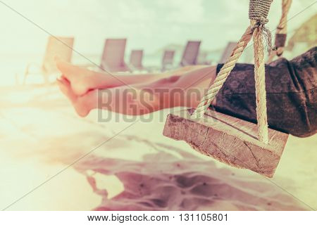 Woman leg on a swing at tropical sea beach - Filtered image processed vintage effect
