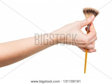 Cosmetic brush for makeup in a female hand isolated on white background.