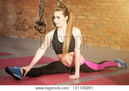 Cheerful young girl is doing splits on flooring in gym. She is looking forward with confidence