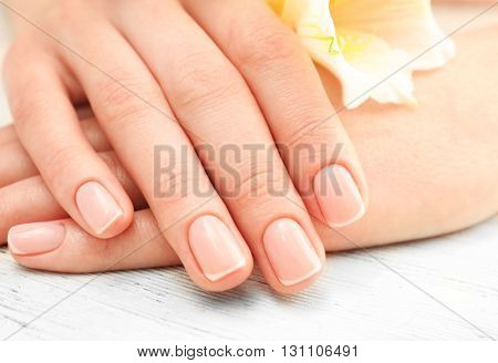 Spa concept. Woman hands with beautiful flowers and nail polish on wooden background, close up