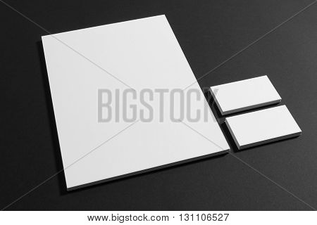 Blank branding mockup on black with letter and business cards.