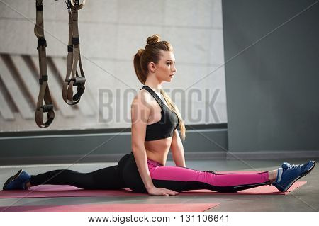 Beautiful young woman is sitting on the string with concentration. Trx fitness straps are hanging behind her