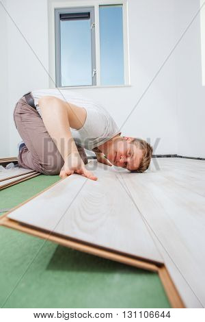 Man installing light laminate flooring in a room
