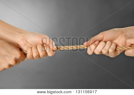 Teamwork concept. People hands pulling the rope on grey background