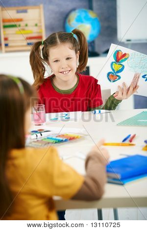 Portrait of elementary age schoolgirl showing colorful paining to classmate in art class in primary school classroom.?