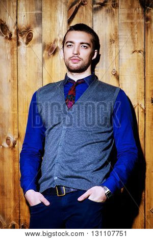 Handsome young man posing by a wooden wall. Business style. Beauty, fashion.