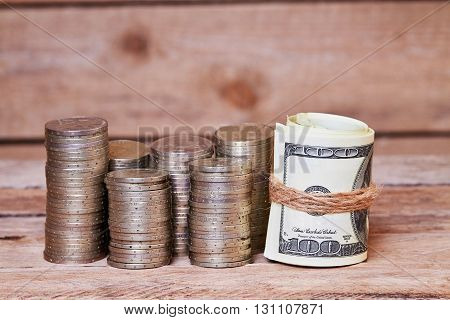 Dollar bills wrapped in jute rope and piles of coins