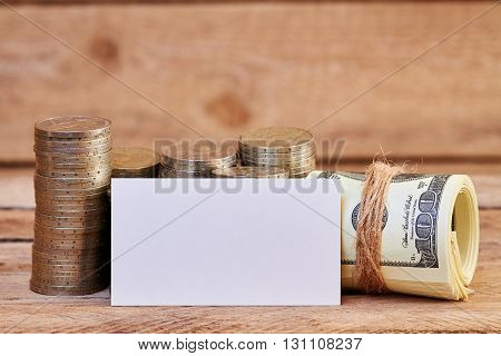 Dollar bills wrapped in jute rope, business card and piles of coins