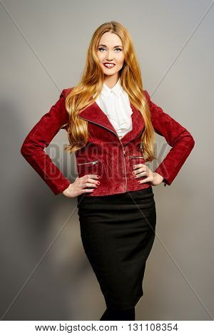 Vogue shot of a beautiful elegant young woman in over grey background. Business style clothes.