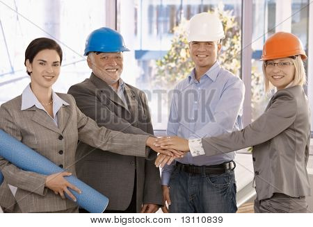 Team portrait of happy architects standing in office, holding hands together expressing teamwork and unity.?