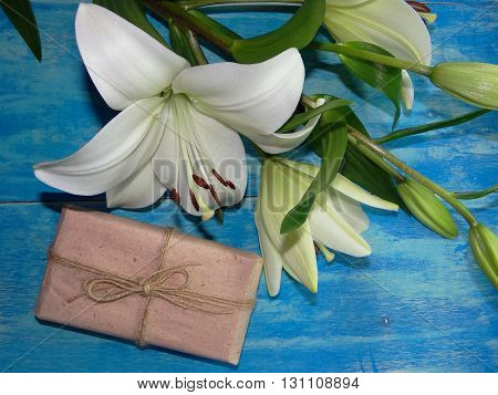beautiful Lily flowers are on blue wooden boards lying next to the gift
