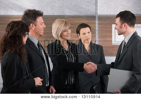 Smiling businessman and businesswoman shaking hands in office.?