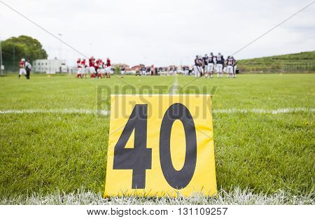 Football yard line with a sign in the foreground