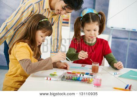 Alumnos de primaria edad sentados disfrutando de pintura con colores en clase de arte en primaria scho de escritorio