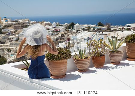 Girl in white hat and blue dress sits in Santorini. Pots with flowers. White houses on the mountain. Sea. Greece. Blue sky.