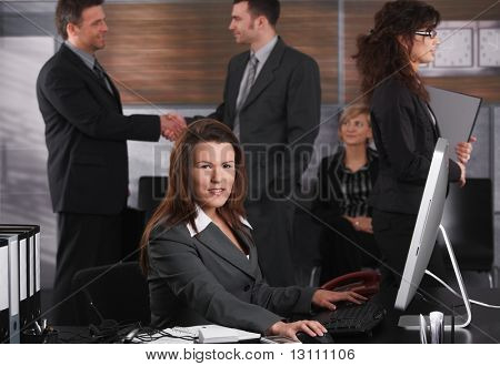 Mid-adult businesswoman dealing with computer tasks sitting at desk in office, looking at camera.?