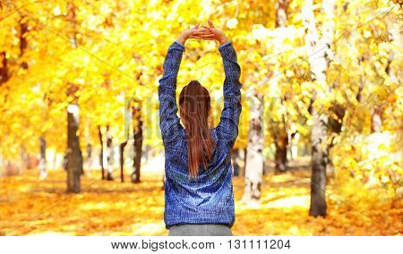 Young beautiful woman doing sport exercises in autumn park