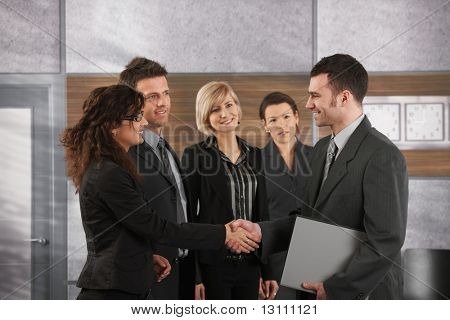Happy businessman introducing himself to business team in office.?