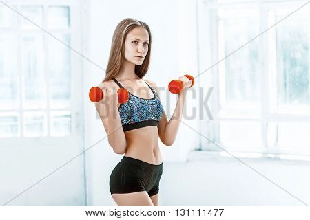 Sporty woman doing aerobic exercise with red dumbbells on white background